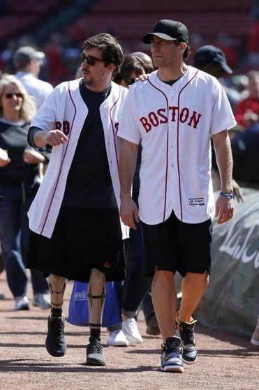 Jeff Bauman (left) walked with actor Jake Gyllenhaal before throwing out the first pitch before the Red Sox game.